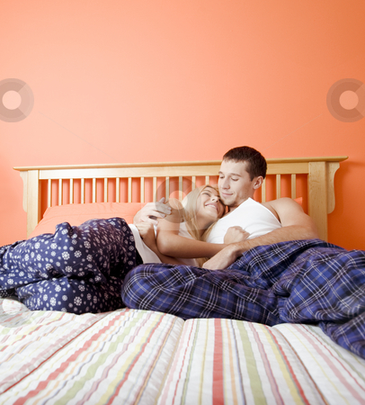 Young Couple in Pajamas Sitting on Bed stock photo, Young couple sitting on bed with stripped bedspread facing each other and embracing. Vertical shot. by Christopher Nuzzaco
