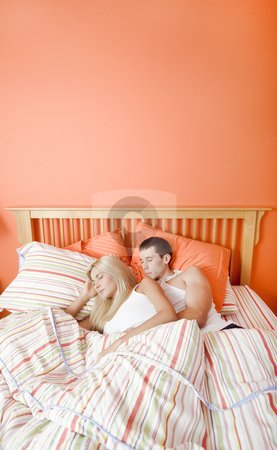 Young Couple Sleeping in Bed stock photo, High angle view of young couple sleeping closely together under a striped bedspread. Vertical shot. by Christopher Nuzzaco