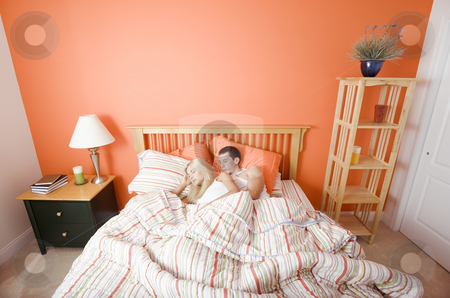Young Couple Sleeping in Bed stock photo, High angle view of young couple sleeping closely together under a striped bedspread. Horizontal shot. by Christopher Nuzzaco