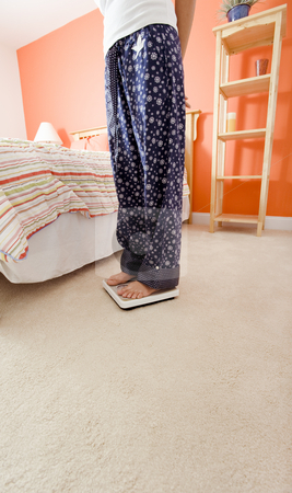 Woman Using Scale in Bedroom stock photo, Cropped view of woman standing on a scale next to her bed. Vertical format. by Christopher Nuzzaco