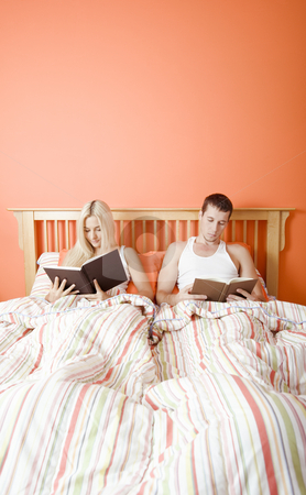 Couple Reading in Bed stock photo, Man and woman reading side-by-side in bed. Vertical format. by Christopher Nuzzaco