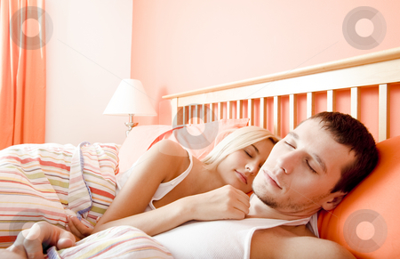 Couple Sleeping in Bed stock photo, Man and woman sleep close together in a brightly-colored bedroom. Horizontal format. by Christopher Nuzzaco