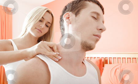 Woman Massaging Man's Shoulders stock photo, Man and woman sit on bed as woman massages man's shoulders. Horizontal format. by Christopher Nuzzaco