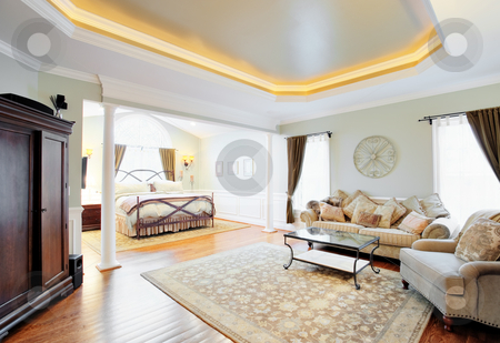 Upscale Master Suite Interior stock photo, View of a sitting area and bed in a master suite with coved ceiling. Horizontal format. by Christopher Nuzzaco
