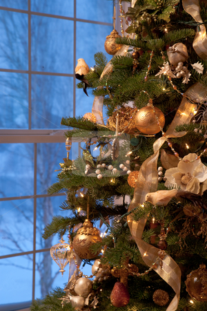 Decorated Christmas Tree stock photo, Side of a ornately decorated Christmas tree in front of a window showing a snowy landscape. Vertical shot. by David Papazian