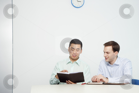 Handsome Young Businessmen Reviewing Day Planner stock photo, Handsome young businessmen review information in day planers.  Horizontal shot. by Paul Burns