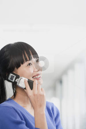 Attractive Young Businesswoman Smiling stock photo, Attractive young businesswoman smiles with a cellphone to her ear. Vertical shot. by Paul Burns