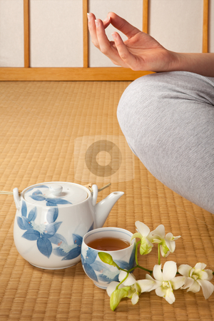 Tea orchids and meditation stock photo, Meditating woman on japanese tatami mat with green tea and orchids by Anneke