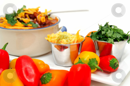 Chili Beans And Peppers stock photo, Chili and beans in a ceramic bowl with onion, cilantro and cheddar cheese sprinkled on with with sides of each in stainless steel condiment cups. by Lynn Bendickson