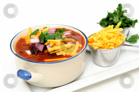 Chili And Beans stock photo, Chili and beans in a ceramic bowl with onion, cilantro and cheddar cheese sprinkled on with with sides of each in stainless steel condiment cups. by Lynn Bendickson