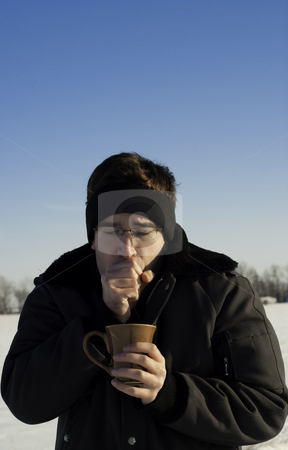 Man Warming His Hands stock photo, A man outside in the winter is warming his hands and holding a cup of coffee by Richard Nelson