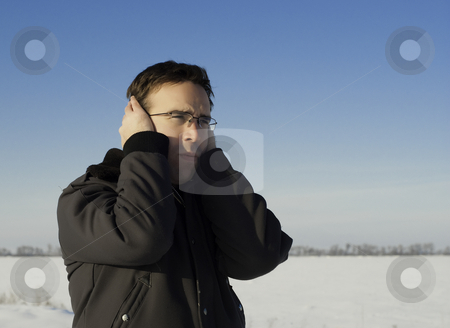 Cold Ears stock photo, A young man standing outside in the winter, holding his ears to keep them warm by Richard Nelson