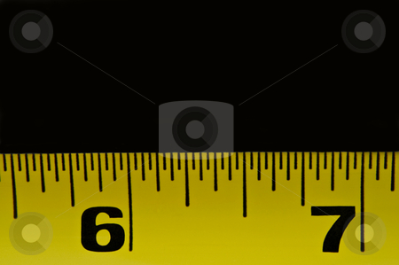 Tape measure stock photo, Close up of a section of yellow metal tape measure arranged in the lower portion of the image with black background. by Samantha Craddock