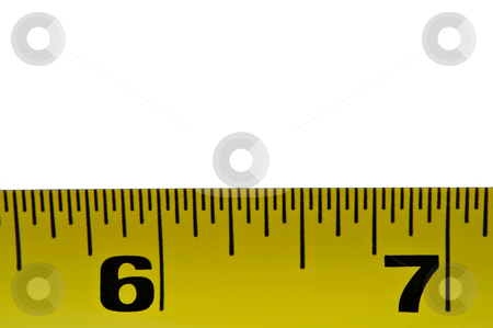 Tape measure stock photo, Close up of a section of yellow metal tape measure arranged in the lower portion of the image with white above by Samantha Craddock