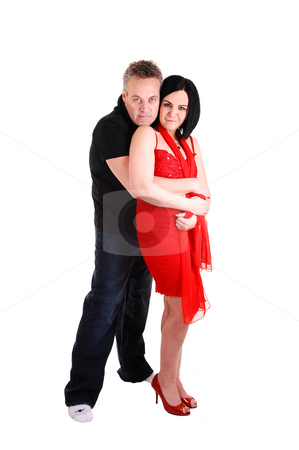 Couple hugging. stock photo, An middle age couple, she in an red dress and black hair get a big hug from her husband from the back, on white background. by Horst Petzold
