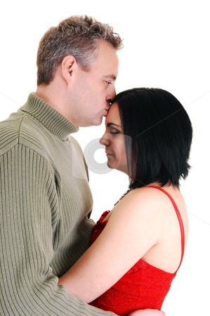 Husband kissing wife. stock photo, A middle age husband gives he wife a kiss of honor on her forehead and holts her in his arms, on white background. by Horst Petzold