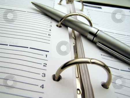 Make a date stock photo, Macro of a pen on a planner by Christy Thompson