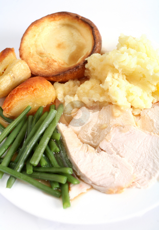 Festive turkey dinner stock photo, A festive dinner with turkey breast, green beans, roast and mashed potatoes and yorkshire pudding by Paul Cowan