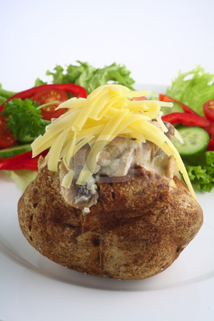 Baked potato with mushroom and cheese stock photo, A baked potato topped with a creamy mushroom sauce and grated cheddar cheese by Paul Cowan