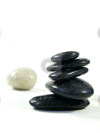 Odd man out stock photo, Rocks carefully stacked isolated on white with a lighter rock out of focus in back. shallow depth of field. focus on bottom of front pile of rocks. by Christy Thompson