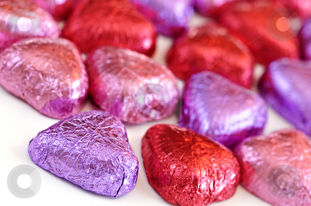Valentine candy stock photo, Valentine's chocolates wrapped in red and purple foil on white background by Elena Elisseeva