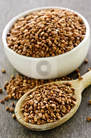 Buckwheat grain stock photo, Buckwheat seeds on wooden spoon and in bowl by Elena Elisseeva
