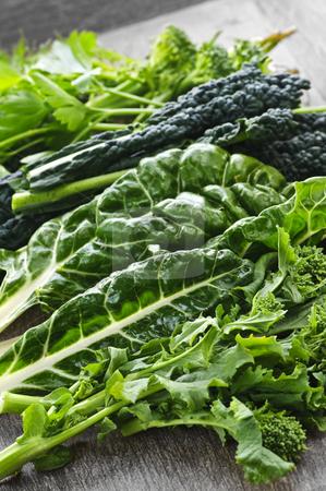 Dark green leafy vegetables stock photo, Dark green leafy fresh vegetables on cutting board by Elena Elisseeva