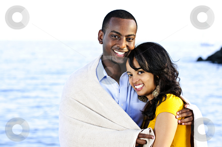 Happy couple sharing blanket stock photo, Young romantic sharing a blanket by the ocean by Elena Elisseeva