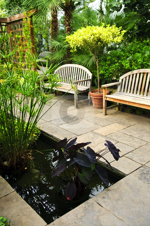 Lush green garden stock photo, Lush green garden with stone landscaping, pond and benches by Elena Elisseeva