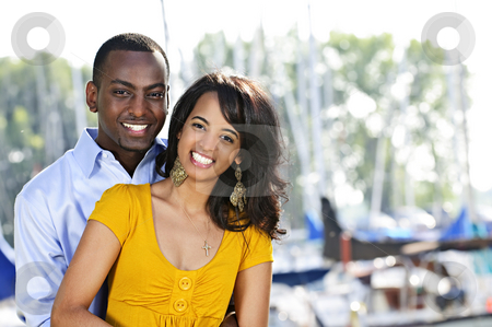 Happy couple hugging stock photo, Young romantic couple hugging and standing at harbor by Elena Elisseeva