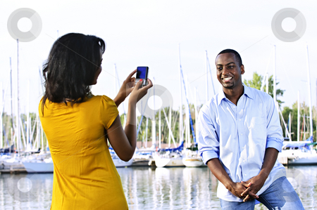 Man posing for picture near boats stock photo, Handsome man posing for vacation photo at harbor with sailboats by Elena Elisseeva