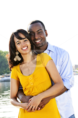 Happy couple at seaside stock photo, Young romantic couple hugging and standing at harbor by Elena Elisseeva