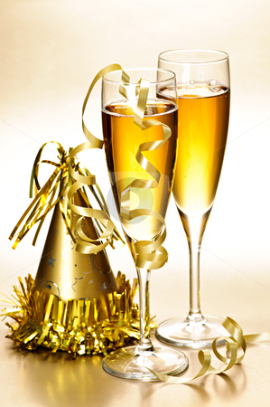 Champagne and New Years party decorations stock photo, Two full champagne flutes with party hat and ribbons by Elena Elisseeva