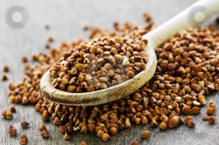 Buckwheat grain stock photo, Buckwheat seeds on wooden spoon in closeup by Elena Elisseeva