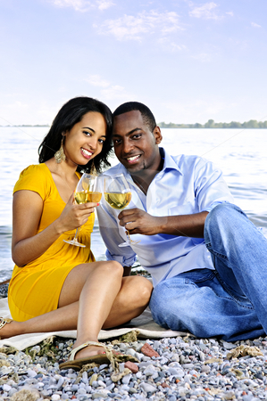 Happy couple having wine on beach stock photo, Young romantic couple celebrating with wine at the beach by Elena Elisseeva