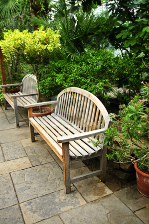Lush green garden stock photo, Lush green garden with stone landscaping and benches by Elena Elisseeva