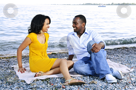 Happy couple sitting at beach stock photo, Young romantic couple looking at each other sitting on beach by Elena Elisseeva