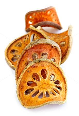 Dried bael fruit stock photo, Slices of dried bael fruit on white background by Elena Elisseeva