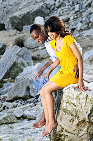 Happy couple sitting at rocky shore stock photo, Happy couple dipping feet in ocean sitting on boulder at rocky shore by Elena Elisseeva