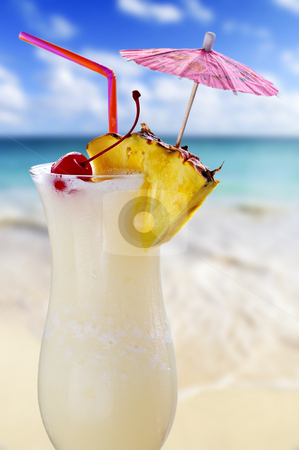 Pina colada cocktail stock photo, Pina colada drink in cocktail glass with tropical beach in background by Elena Elisseeva