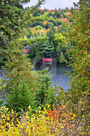 Fall forest and lake stock photo, Boathouse on lake through fall forest with colorful trees by Elena Elisseeva