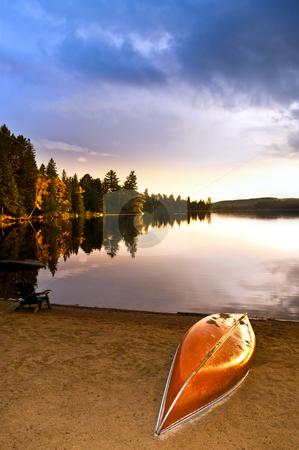 Lake sunset with canoe on beach stock photo, Canoe on beach at sunset on lake shore by Elena Elisseeva