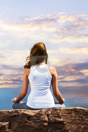 Young girl meditating at sunset stock photo, Portrait of young teenage girl practicing yoga at sunset by Elena Elisseeva