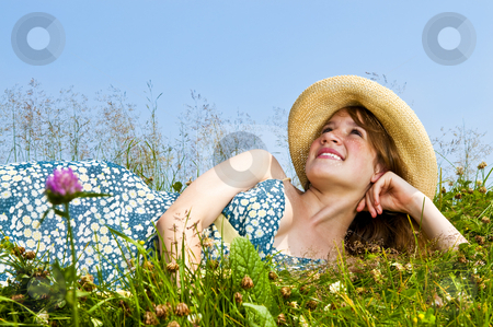 Young girl laying in meadow stock photo, Young teenage girl laying on summer meadow in straw hat looking up by Elena Elisseeva