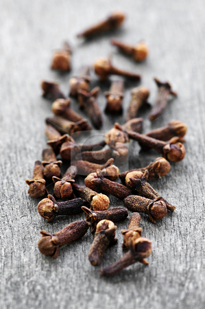 Cloves stock photo, Several dried clove buds on wooden background by Elena Elisseeva