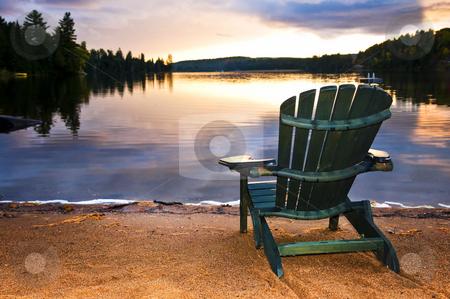 Wooden chair at sunset on beach stock photo, Wooden chair on beach of relaxing lake at sunset by Elena Elisseeva