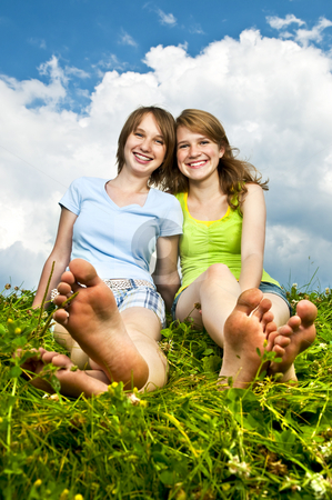 Young girls sitting in meadow stock photo, Two young teenage girl friends sitting barefoot on summer meadow by Elena Elisseeva