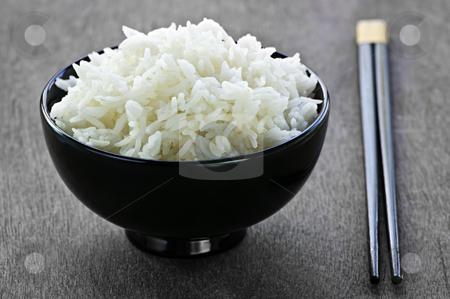 Rice bowl with chopsticks stock photo, White steamed rice in black round bowl with chopsticks by Elena Elisseeva