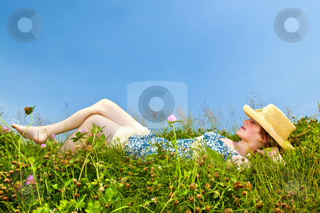 Young girl laying in meadow stock photo, Young teenage girl laying barefoot on summer meadow in straw hat by Elena Elisseeva