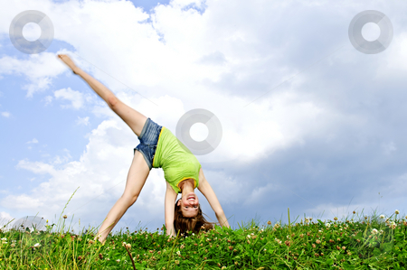 Young girl doing cartwheel stock photo, Young teenage girl doing cartwheel in a summer meadow by Elena Elisseeva